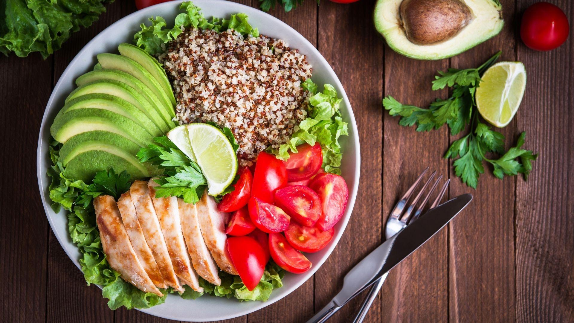nutritious meal containing chicken, avocado, lettuce, tomato & quinoa