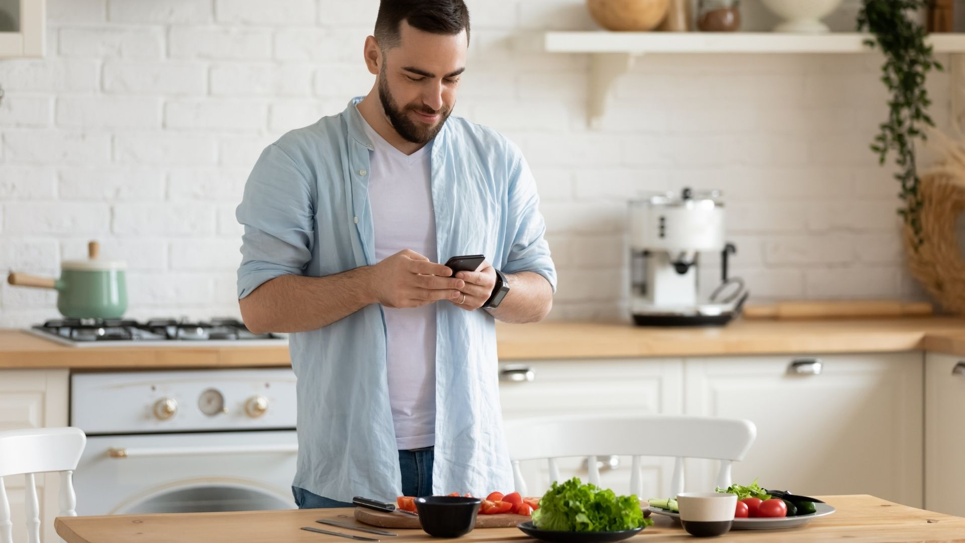 man tracking his calories and macros whilst he preps his food