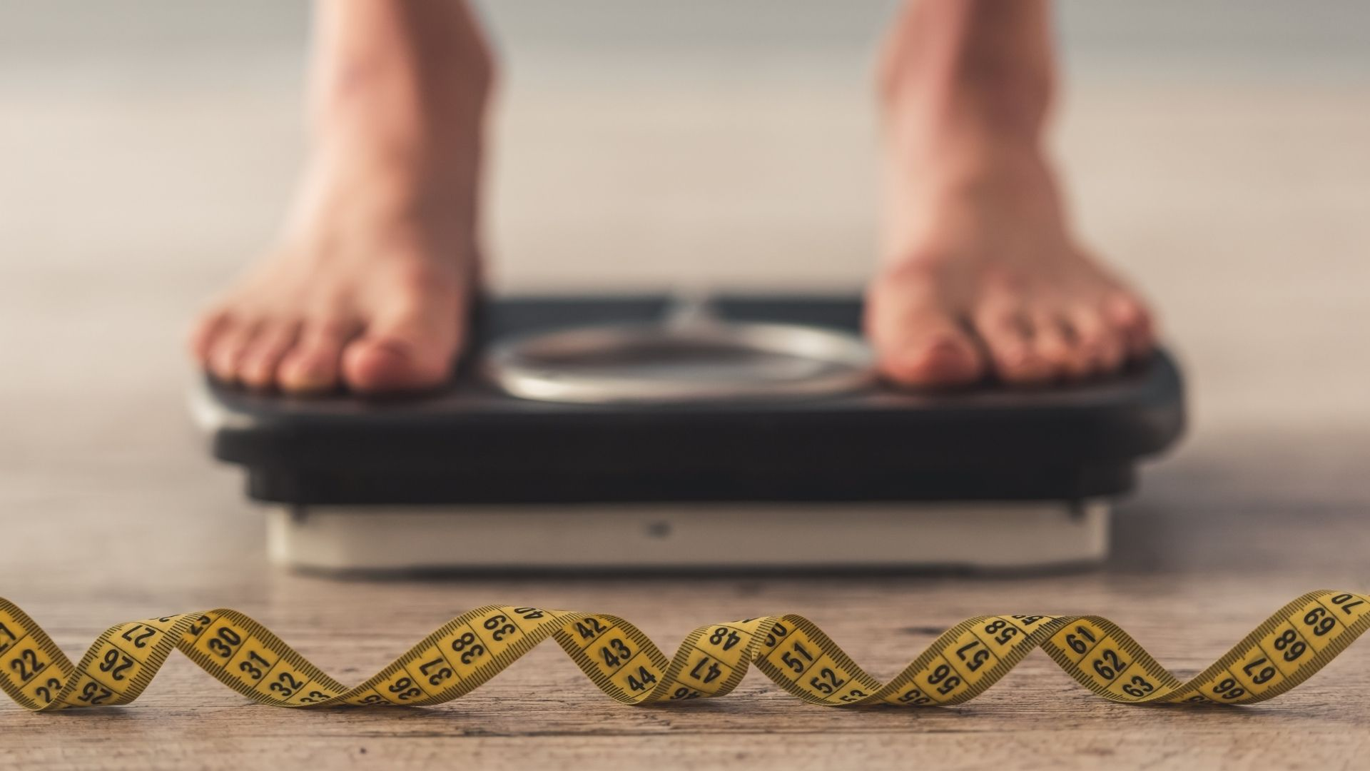 man on weight scale with measuring tape to track his fat loss