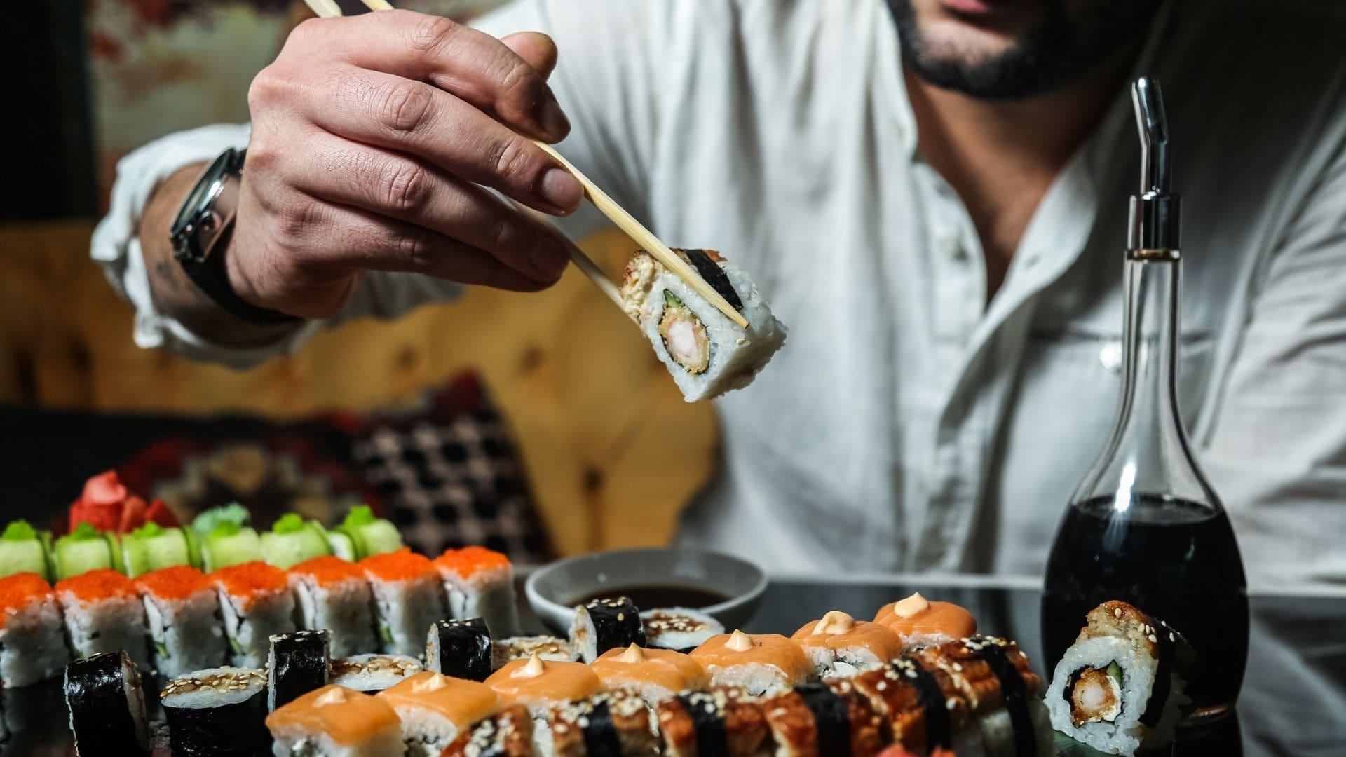 man eating sushi plate of salmon nigiri, California roll and soy sauce